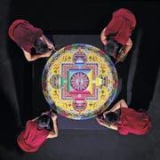 Viel Zeit und Geduld: Tibetische Mönche beim Streuen eines Mandalas. (Bild: PD)