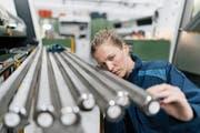 Eine Mitarbeiterin eines Metallbaubetriebs kontrolliert Stahlrohre. (Bild: Kniel Synnatschke/Westend61)