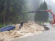 Spektakuläre Rettungsaktion in Splügen: Zwei Autoinsassen werden mit einem Kran aus dem reissenden Bach geborgen. (Bild: Kapo GR)