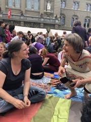 Iris Käser (rechts) im Gespräch mit einer Frau, die am Weltentuch näht.