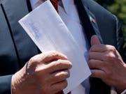 US-Präsident Donald Trump zeigte am Dienstag den zusammengefalteten Brief Journalisten vor seiner Abreise an einen Wahlkampfauftritt im US-Staat Iowa. (Bild: KEYSTONE/AP/EVAN VUCCI)