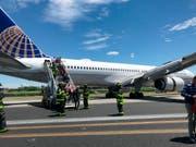 Rettungspersonal hilft bei der Evakuierung eines Flugzeugs der United Airlines, das auf dem Flughafen Newark bei New York teilweise von der Landebahn abgekommen ist. (Caroline Craddock via AP) (Bild: KEYSTONE/AP Caroline Craddock)