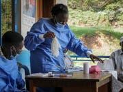 Das Gesundheitspersonal zieht in einem Spital im Westen Ugandas Schutzkleidung an, bevor es mit dem Impfen von Menschen gegen Ebola beginnt. (AP Photo/Ronald Kabuubi) (Bild: KEYSTONE/AP/RONALD KABUUBI)