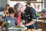 Tipps vom Starkoch: Im Oberstufenzentrum Buechenwald zeigt Rolf Caviezel den Kindern, worauf es beim Kochen ankommt. (Bild: Michel Canonica)