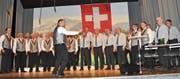 Die Männerchöre von Kobelwald (mit den orangen Krawatten) und Kriessern (mit den blauen Krawatten) verabschiedeten sich unter der Leitung von Mathias Wachter gemeinsam mit wohlklingendem Gesang. (Bild: René Jann)