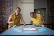 Pema Wangyal (links) ist einer von drei tibetischen Mönchen, die derzeit im Historischen und Völkerkundemuseum in St.Gallen an einem Sandbild arbeiten. (Bild: Adriana Ortiz Cardozo)
