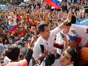 Venezuelas Oppositionsführer Juan Guaidó (Mitte) hat am Samstag seinen Anhängern erneut Mut gemacht, dass die Regentschaft von Staatschef Nicolás Maduro bald zu Ende sein werde. (Bild: KEYSTONE/AP/ARIANA CUBILLOS)