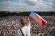 Ein Mann weht mit der tschechischen Flagge vor den hunderttausend Demonstranten, die sich am Sonntag in Prag versammelt haben. Bild: Martin Divisek/EPA (Prag, 23. Juni 2019)