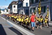 Hinter dem Hornträger und den Fahnenträgern laufen Verein und Dorfbewohner. (Bild: pd)