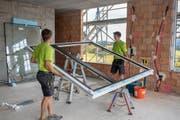 Mitarbeitende der Edelweiss Fenster AG bauen ein Fenster ein. (Bild: PD)