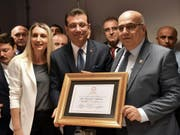 Der neue Bürgermeister von Istanbul, Ekrem Imamoglu (Mitte), präsentiert seine Ernennungsurkunde. (Bild: KEYSTONE/AP Pool Imamoglu Press Team)