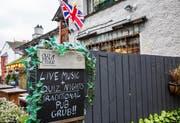 Ein klassisches Pub im nordenglischen Bowness-on-Windermere wirbt für sein altbewährtes Programm.Bild: Martin Berry/Alamy