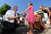 Schulpräsident Christoph Kohler nimmt von einer Kindergärtlerin einen Glückskäfer entgegen, damit der Neubau gut gelinge. (Bild: Manuel Nagel)