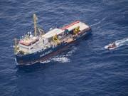 Ein Boot holt zwei Flüchtlinge vom Rettungsschiff Sea Watch 3, das vor Lampedusa blockiert ist. (Bild: KEYSTONE/EPA SEA-WATCH/SEA-WATCH HANDOUT)