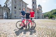 Stefan Küng (links) und Claudio Imhof posieren zusammen mit einem Teamhelfer vor der Klosterkirche Einsiedeln. (Bild: Urs Flüeler / Keystone, 4. Juni 2019)