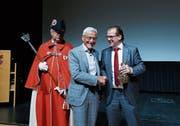 Gemeindepräsident Georges Helfenstein (rechts) überreicht Josef Huwiler den bronzenen Bären der Sparte Wirtschaft. Links im Bild Gemeindeweibel Peter Stalder. (Bild: Stefan Kaiser (Cham, 5. Juni 2019))