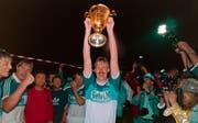 Jürgen Mohr stemmt am 10. Juni 1989 nach dem 1:0-Heimsieg gegen Servette auf der Luzerner Allmend den Meisterpokal in die Höhe. (Bild: Keystone)