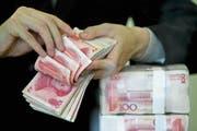 Ein Bündel chinesischer Banknoten in einer Bank in Wuhan. Chinesische Unternehmen sind nach wie vor auf Einkaufstour in Europa und der Schweiz. (Bild: AP)