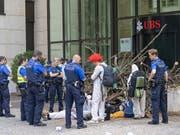 Polizisten räumten am Montag die Blockade der Aktivisten einer Gruppe namens «Collective Climate Justice» vor dem UBS-Bürogebäude am Aeschenplatz in Basel. Im Hintergrund eine Holzbeige, die an Schwemmholz erinnert, als Sperre vor der Türe. (Bild: KEYSTONE/GEORGIOS KEFALAS)