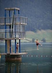 Nicht alle Besucher des Freibads halten sich wie diese zwei Buben an das Verbot, von der Fünfmeterplattform ins Wasser zu springen. Bild: Stefan Kaiser (Oberägeri, 9. Juli 2019)