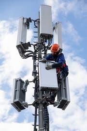 Ein Swisscom-Mitarbeiter installiert ein Element einer 5G-Antenne. (Bild: KEYSTONE/Peter Klaunzer)