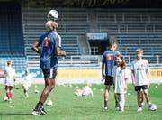 FCL-Goalgetter Blessing Eleke jongliert den Ball auf der Stirn, die Kids schauen bewundernd zu. Bild: Manuela Jans-Koch (Luzern, 14. Juli 2019)