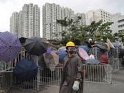 Die Demonstranten blockieren eine Strasse im Honkonger Distrikt Sha Tin. (Bild: Keystone/AP/KIN CHEUNG)