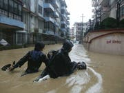 Nepalesen waten mit ihrem Motorrad durch die überfluteten Strassen der Hauptstadt Kathmandu. (Bild: Keystone/AP/NIRANJAN SHRESTHA)