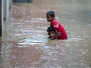Ein Mann trägt seinen jüngeren Bruder durch eine überschwemmte Strasse in der nepalesischen Hauptstadt Kathmandu. (Bild: KEYSTONE/EPA/NARENDRA SHRESTHA)