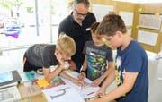 Architekt Felix Rutishauser rechnet mit drei jungen Teilnehmern Planmassstäbe um. (Bild: Christof Lampart)