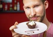 Daniel Birchler mit einem knusprigen Cupcake aus Grillenmehl. Bild: Urs Bucher