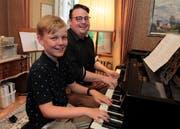 Der jüngere (Moritz Raab) und der ältere (Reto Bugmann) Vinzenz setzen sich fürs gemeinsame Foto ans Klavier. (Bild: Florian Arnold, Altdorf, 2. Juli 2019)