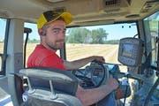 Stefan Pichel fährt mit seinem Traktor über ein abgeerntetes Getreidefeld und presst dabei Strohballen. (Bild: Mario Testa)