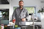 Michael Vogt, Präsident des Kochklubs Thurchuchi, steht in seiner Küche in Sulgen und schneidet Gemüse.Bild: Yvonne Aldrovandi-Schläpfer