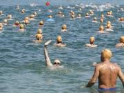 Die Seeüberquerung ist kein Wettbewerb mit Zeitmessung. Da bleibt auch Zeit, um dem Fotografen zuzuwinken. (Bild: KEYSTONE/ENNIO LEANZA)