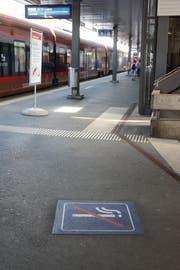 Symbole am Boden und Infoblätter auf den Perrons weisen auf das Rauchverbot hin. (Bild: Alessia Pagani)