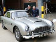 Schauspieler Daniel Craig und Prinz Charles freuen sich am Aston Martin «Bond-Auto» - weniger Freude haben derzeit allerdings die Aktionäre des Autoherstellers an ihren Papieren. (Bild: KEYSTONE/AP PA/CHRIS JACKSON)