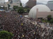 In Hongkong haben erneut Zehntausende gegen das umstrittene Auslieferungsgesetz protestiert - diesmal vor dem Schnellzugbahnhof für Verbindungen auf das chinesische Festland, um auch chinesische Touristen auf ihr Anliegen aufmerksam zu machen. (Bild: KEYSTONE/AP/KIN CHEUNG)