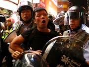 Polizisten in Hongkong führen am Sonntag einen Demonstranten ab. (Bild: KEYSTONE/AP/VINCENT YU)
