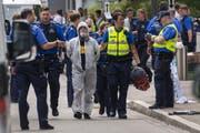 Polizisten räumen die Blockade der Aktivisten vor der UBS am Aeschenplatz in Basel. (Bild: Keystone/Georgios Kefalas)