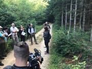 Projektleiterin Isabelle Glanzmann (oben, mit Unterlagen) erläutert vor Medien im Gelterkinder Wald den Nutzen der Ameisen und derer Inventarisierung. Rechts mit gelbem Pfosten markiert ist ein kleiner Ameisenhaufen unter einem Jungbaum. (Bild: Roger Lange Morf, Keystone-SDA)