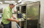 Ein Küchenmitarbeiter füllt einen der Regenerationswagen mit den bestückten Tabletts. Induktionsspulen erwärmen später das Essen. (Bild: Reto Martin)