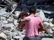 Durch Luftangriffe zerstört: In der Provinz Idlib sollen nun die Waffen schweigen. Ein Mann trägt in der Stadt Ariha ein verletztes Kind weg. (Bild: KEYSTONE/AP Syrian Civil Defense White Helme)