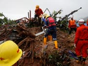 Nach einem Erdrutsch in Myanmar suchten Rettungskräfte am Samstag nach Vermissten. Offiziellen Angaben zufolge könnten noch bis zu 100 Menschen verschollen sein. (Bild: KEYSTONE/EPA/LYNN BO BO)