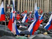 In Moskau trotzen tausende Menschen dem Regen und demonstrieren gegen Polizeigewalt und für faire und freie Wahlen. (Bild: KEYSTONE/AP/ALEXANDER ZEMLIANICHENKO)