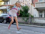 Sprung in eine neue Ära: Voller Freude hüpft diese Erstklässlerin dem ersten Schultag entgegen. (Bild: KEYSTONE/WALTER BIERI)