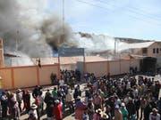 Aus Protest gegen eine kanadische Silbermine in Peru setzten Demonstranten im Mai 2011 mehrere Gebäude in der Provinz Puno in Brand. (Bild: KEYSTONE/EPA/STR)
