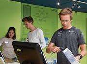 Langläufer Beda Klee (rechts) und Musiker Nickless erhalten an der Kasse Informationen zu den Produkten, welche sie ausgewählt haben. (Bild: Michael Hehli)