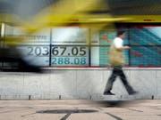 Nicht nur in der Schweiz sind die Börsenkurse gesunken, auch in Asien. Im Bild: Kursanzeige bei einer Bank in Tokio. (Bild: KEYSTONE/AP/EUGENE HOSHIKO)
