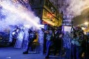 Ein alltägliches Bild: Polizisten schiessen mit Tränengas auf Demonstranten in Hongkong. (Bild: Thomas Peter/Reuters, 14. August 2019)